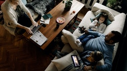 High angle view of family using various technologies in living room at home