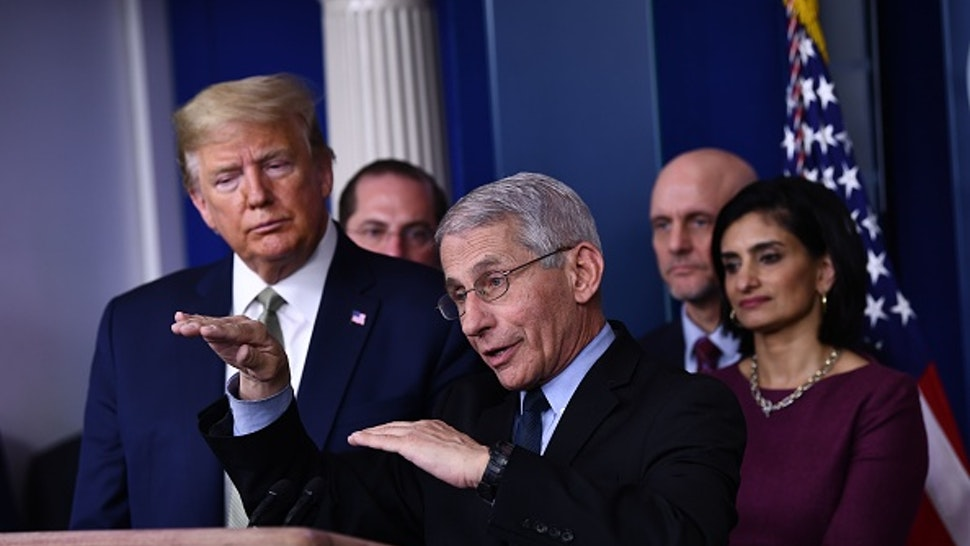 Dr. Anthony Fauci speaks as US President Donald Trump listens during the daily press briefing on the Coronavirus pandemic situation at the White House on March 17, 2020 in Washington, DC. - The coronavirus outbreak has transformed the US virtually overnight from a place of boundless consumerism to one suddenly constrained by nesting and social distancing.The crisis tests all retailers, leading to temporary store closures at companies like Apple and Nike, manic buying of food staples at supermarkets and big-box stores like Walmart even as many stores remain open for business -- albeit in a weirdly anemic consumer environment.