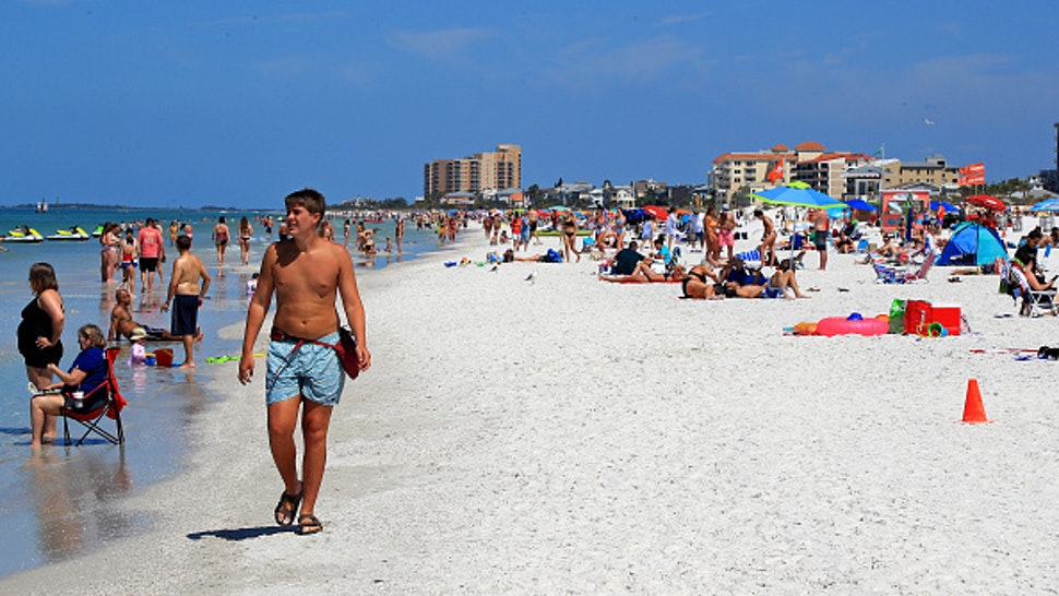 CLEARWATER, FL - MARCH 18: People gather on Clearwater Beach during spring break despite world health officials' warnings to avoid large groups on March 18, 2020 in Clearwater, Florida. The World Health Organization declared COVID-19 a global pandemic on March 11.