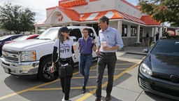 U.S. Senate candidate Rep. Beto O'Rourke (D-TX) (R) talks with his Logistics and Events Manager Cynthia Cano (L) as his Communications Director Chris Evans live streams them leaving lunch at a Whataburger November 3, 2018 in Dallas, Texas.
