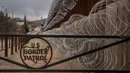 TOPSHOT - A metal fence marked with the US Border Patrol sign prevents people to get close to the barbed/concertina wire covering the US/Mexico border fence, in Nogales, Arizona, on February 9, 2019. (Photo by Ariana Drehsler / AFP) (Photo credit should read ARIANA DREHSLER/AFP via Getty Images)