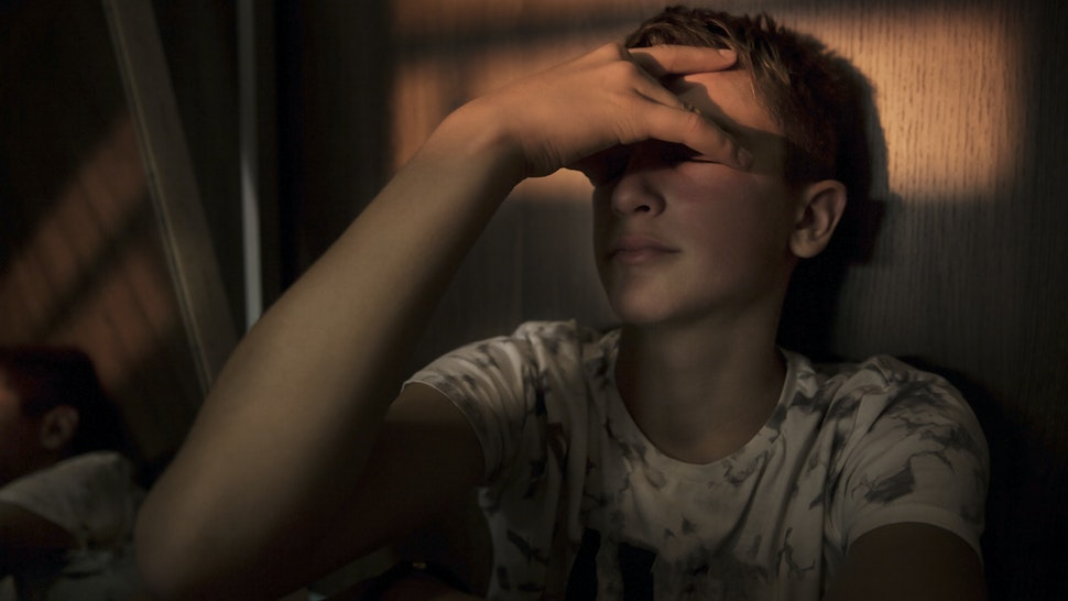 portrait of a teenager boy sitting in the dark room, with a beam of light over his eyes