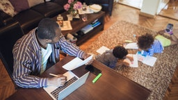 Father working from home while his two children are playing in the living room