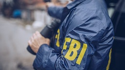 An FBI agent uses a gun in action - stock photo