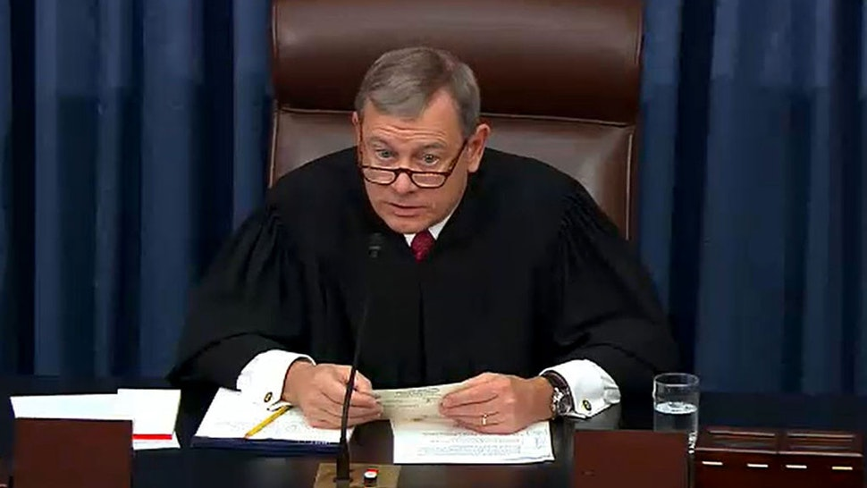 In this screengrab taken from a Senate Television webcast, Chief Justice John Roberts reads a question from a senator during impeachment proceedings against U.S. President Donald Trump in the Senate at the U.S. Capitol on January 29, 2020 in Washington, DC.