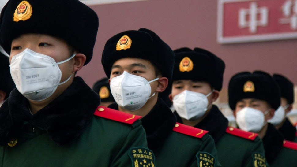 Chinese police officers wearing masks stand in front of the Tiananmen Gate on January 26, 2020 in Beijing, China.