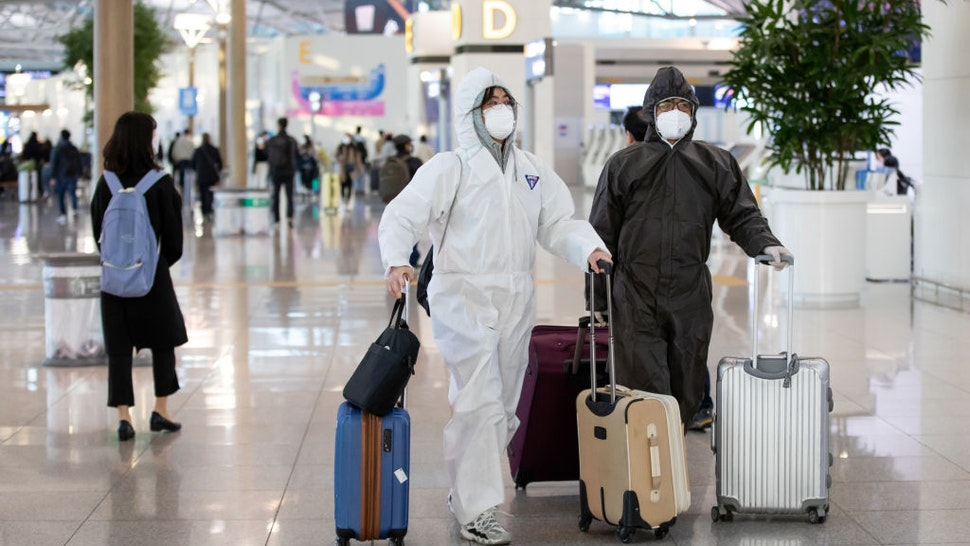 Travelers wearing protective masks and suits walk through Incheon International Airport in Incheon, South Korea, on Monday, March 9, 2020.