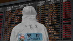 TOPSHOT - An airport security worker wearing protective gear, amid concerns of the COVID-19 coronavirus, looks at a screen showing international departures at Shanghai Pudong International Airport in Shanghai in March 19, 2020. - China on March 19 reported no new domestic cases of the coronavirus for the first time since it started recording them in January, but recorded a spike in infections from abroad. (Photo by Hector RETAMAL / AFP) (Photo by HECTOR RETAMAL/AFP via Getty Images)