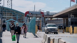 Residents exit US Customs and Border Protection at the Paso del Norte International Bridge during a shut-down of non-essential travel to control the corona virus, COVID-19, outbreak in El Paso, Texas on March 21, 2020.
