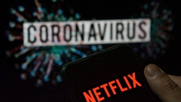 In this photo illustration the American global on-demand Internet streaming media provider Netflix logo seen displayed on a smartphone with a computer model of the COVID-19 coronavirus on the background.