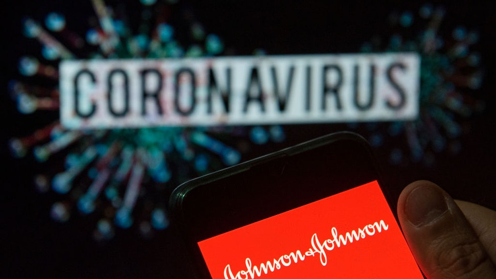In this photo illustration the American multinational medical devices and pharmaceutical company Johnson & Johnson logo seen displayed on a smartphone with a computer model of the COVID-19 coronavirus on the background.