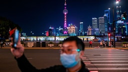 A man wearing a facemask as a preventive measure against the COVID-19 novel coronavirus takes a video of the Bund along the Huangpu River in Shanghai on March 24, 2020.