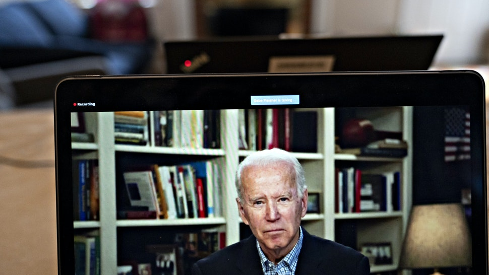 Former Vice President Joe Biden, 2020 Democratic presidential candidate, listens to a question during a virtual press briefing on a laptop computer in this arranged photograph in Arlington, Virginia, U.S., on Wednesday, March 25, 2020. During the livestreamed news conference today, Biden said he didn't see the need for another debate, which the Democratic National Committee had previously said would happen sometime in April. Photographer: Andrew Harrer/Bloomberg via Getty Images