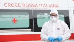 A volunteer wears the protections imposed by the Italian government against coronavirus on March 14, 2020 in Olbia, Italy.