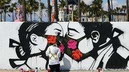VENICE, CALIFORNIA - MARCH 21: Artist Pony Wave paints a scene depicting two people kissing while wearing face masks on Venice Beach on March 21, 2020 in Venice, California. California Governor Gavin Newsom issued a 'stay at home' order for California's 40 million residents in order to slow the spread of coronavirus (COVID-19). Californians may still go to the beach without violating Newsom's order as long as they maintain social distancing and adhere to other public health measures related to the coronavirus. (Photo by Mario Tama/Getty Images)