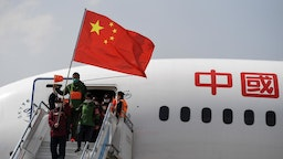 Medical assistance team members holding Chinese Flags take off a plane at Kunming Changshui International Airport on March 22, 2020 in Kunming, Yunnan Province of China.