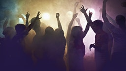 Crowd of people at concert waving arms in the air - stock photo