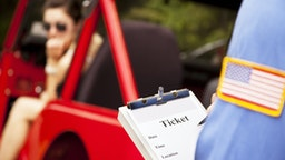Female driver in red vehicle getting traffic ticket from policeman. - stock photo