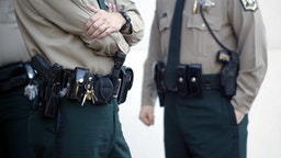 """""""police officers stand with handguns, stun gun and tools on their holsters."""""""