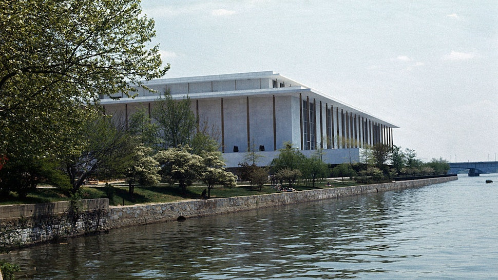 Exterior views of the John F. Kennedy Center for the Performing Arts. The building is situated at river's edge and is surrounded by trees.