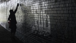 Side view of person spray painting on wall - stock photo