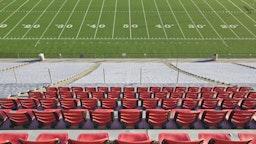 Empty football field and stadium seats. - stock photo