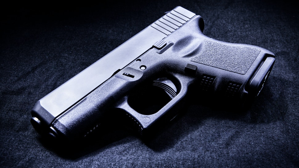 Handgun in a dark room lit by a single light source