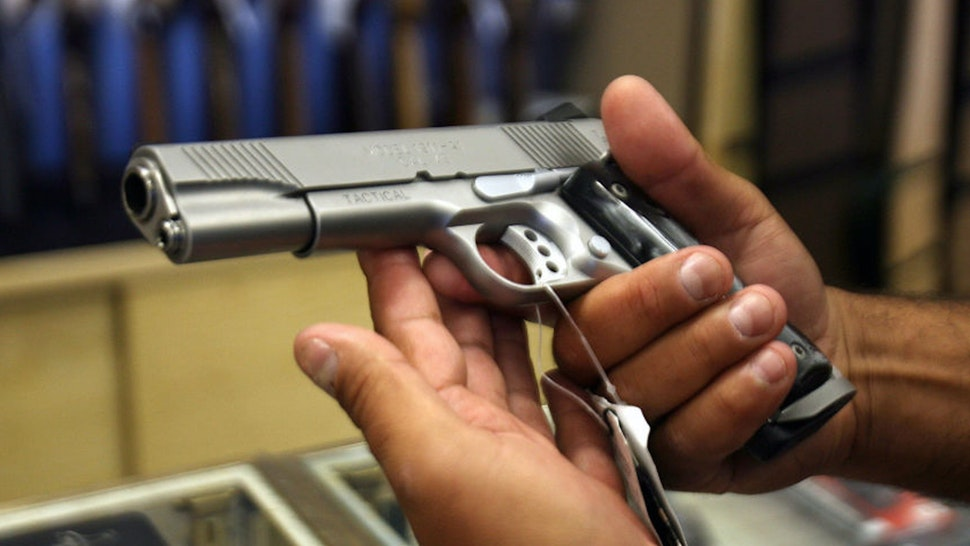 Glendale, UNITED STATES: A man chooses a gun at the Gun Gallery in Glendale, California, 18 April 2007.