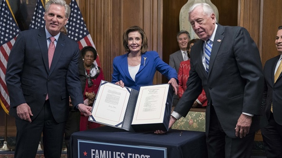 U.S. House Minority Leader Kevin McCarthy, a Republican from California, from left, House Speaker Nancy Pelosi, a Democrat from California, and House Majority Leader Steny Hoyer, hold H.R. 748, Coronavirus Aid, Relief, and Economic Security (CARES) Act, during a ceremony in the Rayburn Room of the U.S. Capitol in Washington, D.C., U.S., on Friday, March 27, 2020. The House approved the largest stimulus package in U.S. history Friday as part of the response to the economic crisis caused by the coronavirus pandemic, sending the measure to President Donald Trump for his signature.