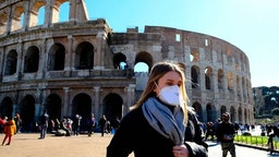 Tourist wearing a protective respiratory mask tours outside the Colosseo monument (Colisee, Coliseum) in downtown Rome on February 28, 2020 amid fear of Covid-19 epidemic. - Since February 23, more than 50,000 people have been confined to 10 towns in Lombardy and one in Veneto -- a drastic measure taken to halt the spread of the new coronavirus, which has infected some 400 people in Italy, mostly in the north.