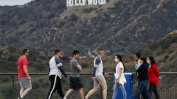 LOS ANGELES, CALIFORNIA - MARCH 22: People, some wearing face masks, walk in Griffith Park with the Hollywood sign behind them on March 22, 2020 in Los Angeles, California. California Governor Gavin Newsom issued a 'stay at home' order for California's 40 million residents in order to slow the spread of coronavirus (COVID-19). Californians may still visit parks without violating Newsom's order as long as they maintain social distancing and adhere to other public health measures related to the coronavirus. Los Angeles Mayor Eric Garcetti today urged Angelenos to practice physical distancing after crowds were seen at some beaches and hiking trails this weekend.