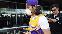 A fan wears a protective mask as people wait in line to attend the 'Celebration of Life for Kobe and Gianna Bryant' memorial service at Staples Center on February 24, 2020 in Los Angeles, California. Los Angeles Lakers NBA star Kobe Bryant, 41, and his 13-year-old daughter Gianna were killed along with seven others in a helicopter crash near Los Angeles on January 26. (Photo by Mario Tama/Getty Images)