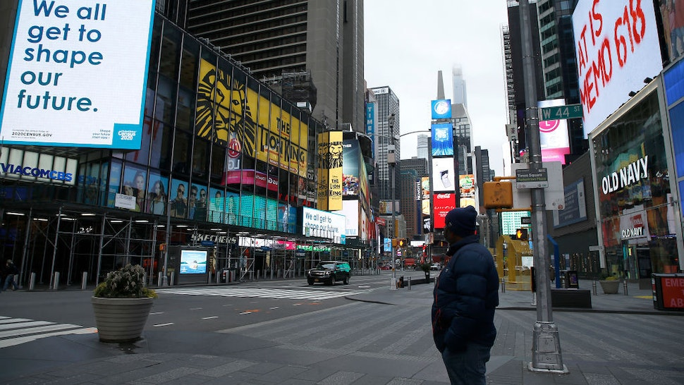 A man takes in the atmosphere in a mostly empty Times Square, New York, US, on March 25, 2020. (Photo by John Lamparski/NurPhoto via Getty Images)