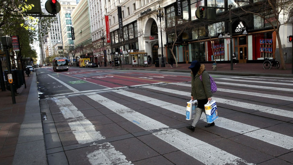 A pedestrian carries two packages of toilet paper as she crosses an empty Market Street on March 17, 2020 in San Francisco, California. Seven San Francisco Bay Area counties have ordered residents to shelter in place in an effort to reduce social interaction and slow the spread of COVID-19. (Photo by Justin Sullivan/Getty Images)