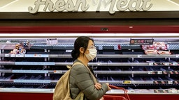 TOKYO, JAPAN - MARCH 27, 2020: A woman wearing a face mask as a precaution against the spread of Coronavirus seen shopping after the Tokyo Local Government have asked citizen to stay home and do not go out unless necessary this coming weekend. Concerns are growing about the increasing cases of Coronavirus (COVID-19) in Japan. Many countries have closed borders to Japan and the growing pandemic has caught public attention on the true number of coronavirus cases in Japan that could be much higher.