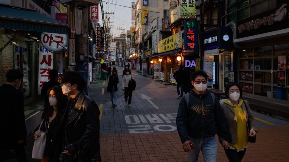 People wearing face masks amid concerns over the COVID-19 novel coronavirus, walk through an alleyway in Seoul on Marh 24, 2020. (Photo by Ed JONES / AFP)