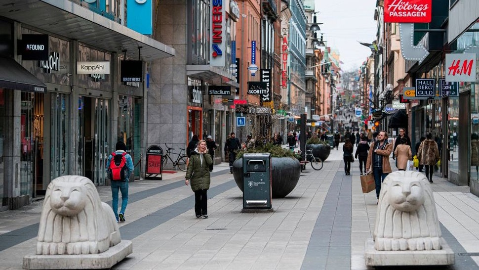 People walk in Drottninggatan in Stockholm, Sweden, where primary schools, restaurants and bars are open and people encouraged to go outside for a nip of air, while the rest of Europe is in lockdown in a bid to curb the spread of COVID-19, on March 24, 2020. - The country's milder tone and measures are in stark contrast to the increasingly alarmist cries from many other countries and international agencies, and have sparked a heated debate in the country about whether Sweden is doing the right thing. (Photo by Jonathan NACKSTRAND / AFP)
