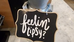 Close-up of comical tip jar with sign with pun reading Feelin Tipsy at Mendocino Farms restaurant in San Ramon, California, December 9, 2019.