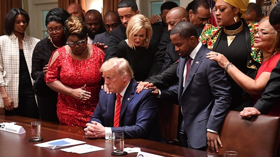 US President Donald Trump (C) stands in a prayer circle during a meeting with African-American leaders in the Cabinet Room of the White House in Washington, DC, on February 27, 2020.