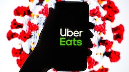Uber Eats logo is displayed on a mobile phone screen photographed on SARS-CoV-2 illustration graphic background. Krakow, Poland on 11th March, 2020.