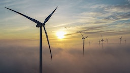 """The sunset glows brightly over wafts of mist behind wind turbines in the """"Odervorland"""" wind farm in the Oder-Spree district. There are currently around 3820 wind turbines with a capacity of 7100 megawatts in the state of Brandenburg. Photo: Patrick Pleul/dpa-Zentralbild/ZB (Photo by Patrick Pleul/picture alliance via Getty Images)"""
