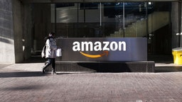A pedestrian walks past the Amazon.com Inc. headquarters in the financial district of Toronto, Ontario, Canada, on Friday, Feb. 21, 2020. Canadian stocks declined with global markets, as authorities struggled to keep thecoronavirus from spreadingmore widely outside China. However, investors flocking to safe havens such as gold offset the sell-off in Canada's stock market. Photographer: