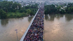 TOPSHOT - Aerial view of a Honduran migrant caravan heading to the US, on the Guatemala-Mexico international border bridge in Ciudad Hidalgo, Chiapas state, Mexico, on October 20, 2018. - Thousands of migrants who forced their way through Guatemala's northwestern border and flooded onto a bridge leading to Mexico, where riot police battled them back, on Saturday waited at the border in the hope of continuing their journey to the United States. (Photo by PEDRO PARDO / AFP) (Photo credit should read