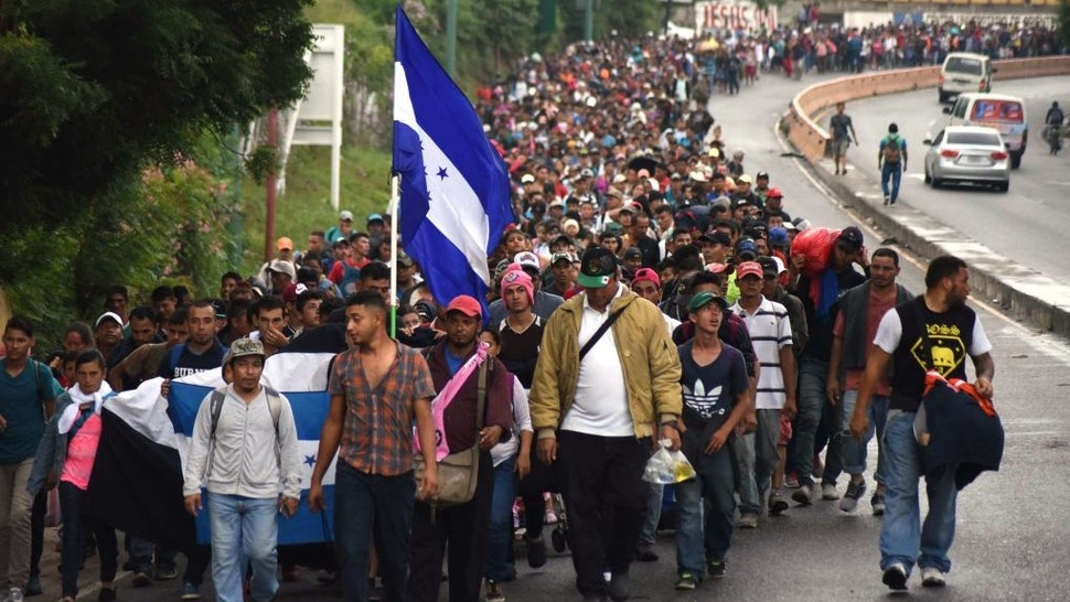 TOPSHOT - Honduran migrants take part in a caravan towards the United States in Chiquimula, Guatemala on October 17, 2018. - A migrant caravan set out on October 13 from the impoverished, violence-plagued country and was headed north on the long journey through Guatemala and Mexico to the US border. President Donald Trump warned Honduras he will cut millions of dollars in aid if the group of about 2,000 migrants is allowed to reach the United States. (Photo by ORLANDO ESTRADA / AFP) (Photo credit should read