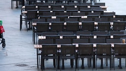 18 March 2020, North Rhine-Westphalia, Cologne: A woman walks past empty tables of a cafe in Cologne. Due to the spread of the coronavirus, many catering establishments are closed indefinitely. Photo: Thomas Banneyer/dpa (Photo by