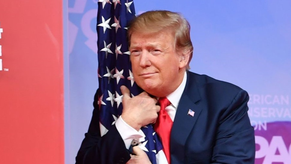 TOPSHOT - US President Donald Trump hugs the US flag as he arrives to speak at the annual Conservative Political Action Conference (CPAC) in National Harbor, Maryland, on March 2, 2019. (Photo by NICHOLAS KAMM / AFP) / ALTERNATIVE CROP (Photo by
