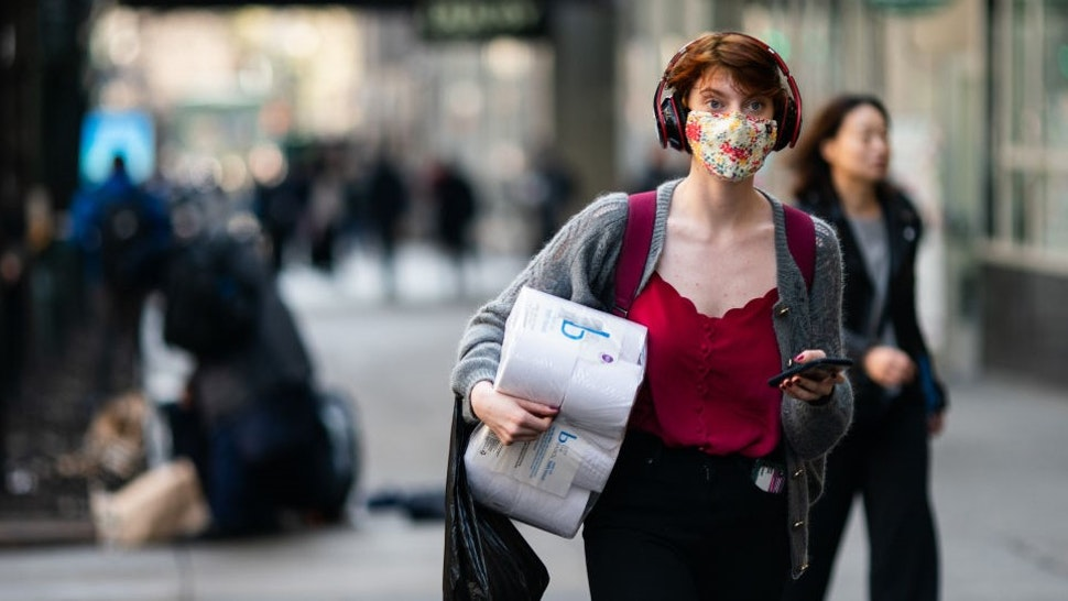 NEW YORK, NY - MARCH 13: A woman wearing a protective mask carries a toilet paper package on the street on March 13, 2020 in New York City. President Donald Trump is expected to declare national emergency over coronavirus crisis today. There are at least 95 confirmed cases in New York City. (Photo by