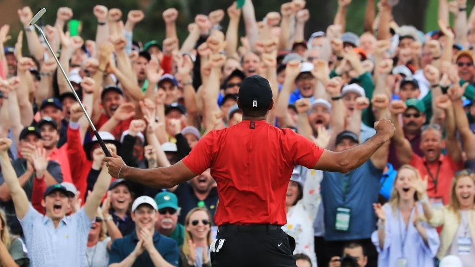 AUGUSTA, GEORGIA - APRIL 14: Patrons cheer as Tiger Woods of the United States celebrates after sinking his putt on the 18th green to win during the final round of the Masters at Augusta National Golf Club on April 14, 2019 in Augusta, Georgia. (Photo by