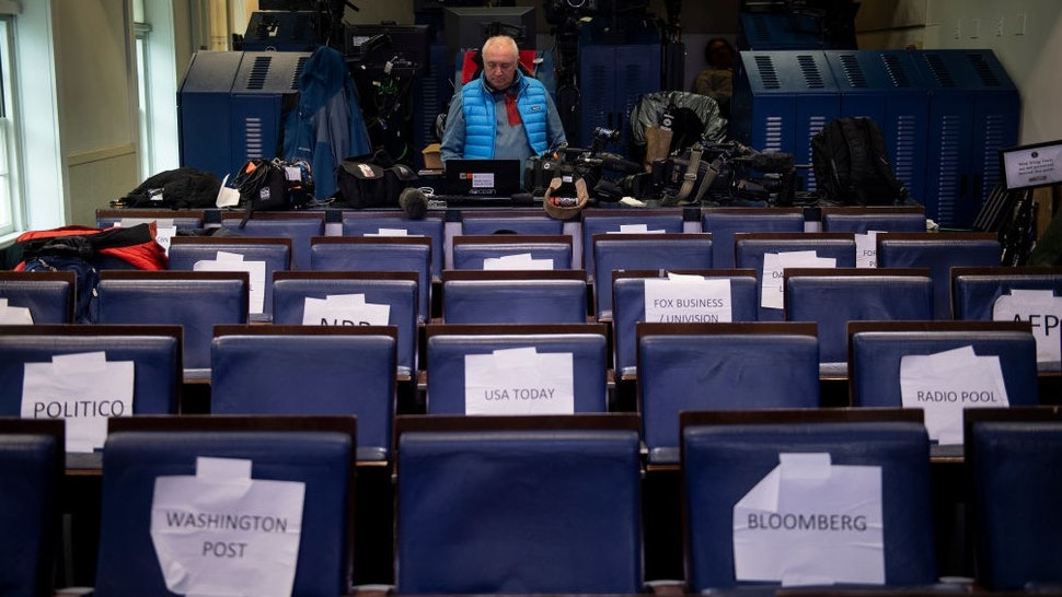 A TV journalist waits in the press briefing room of the White House March 23, 2020, in Washington, DC. (Photo by Brendan Smialowski / AFP) (Photo by