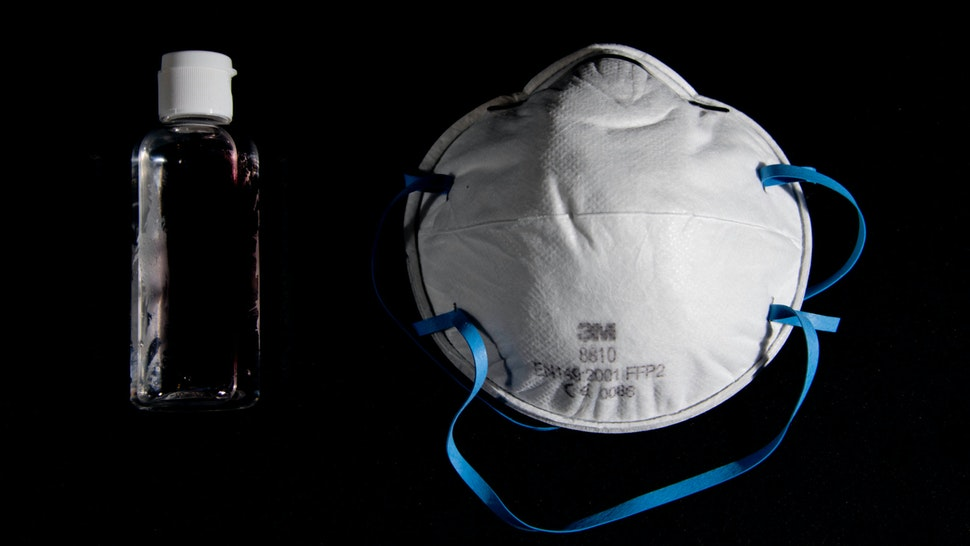 A picture taken on March 4, 2020, in Paris, shows a bottle of alcohol gel hand sanitiser and an FFP2 protective face mask. - Sales of face masks and hand sanitiser have risen and shortages are occuring in countries affected by the spread of COVID-19, the new coronavirus.